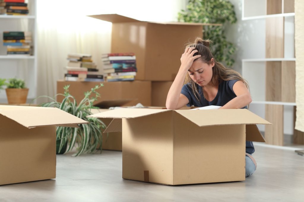 A nervous woman sitting beside a container