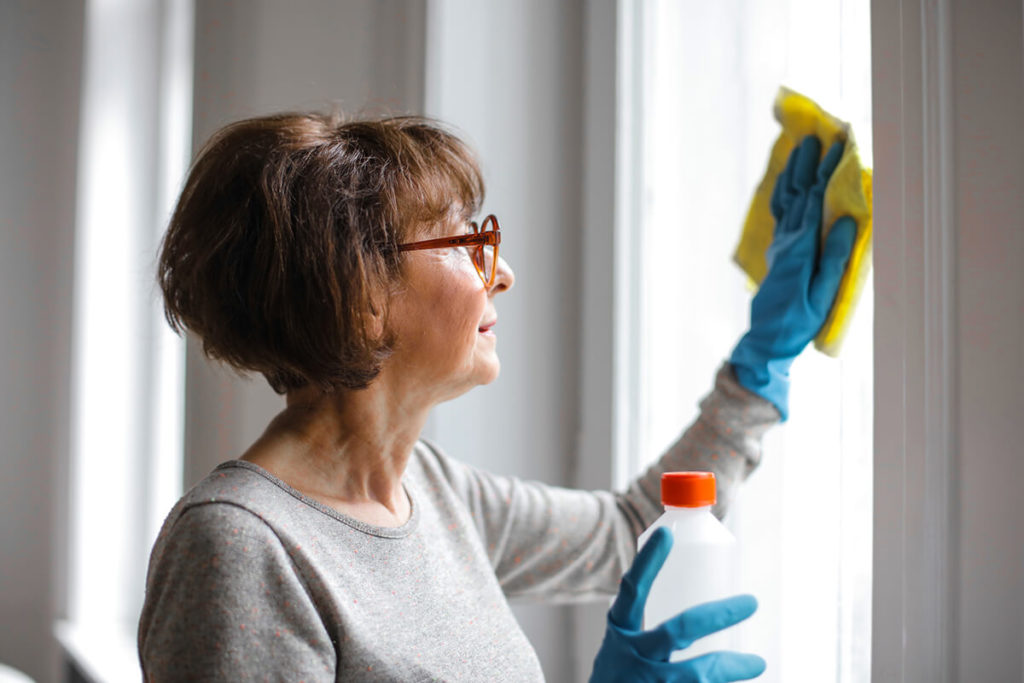 a woman with blue gloves cleaning a window
