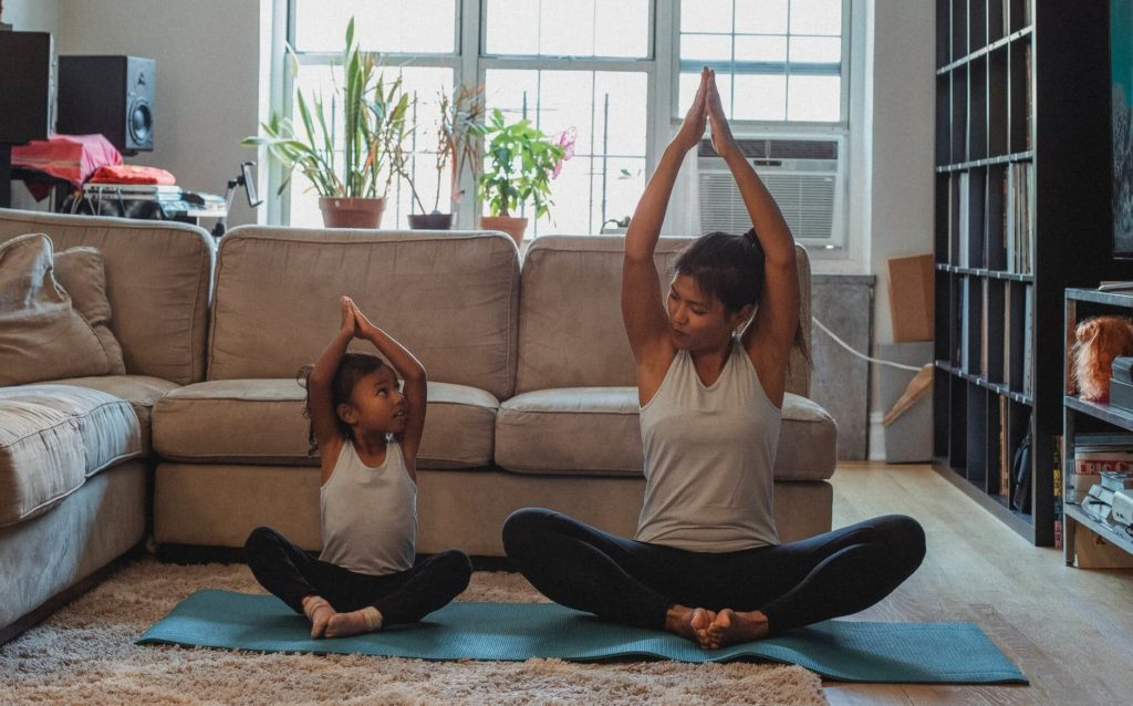 A mother and daughter are doing yoga together and smiling