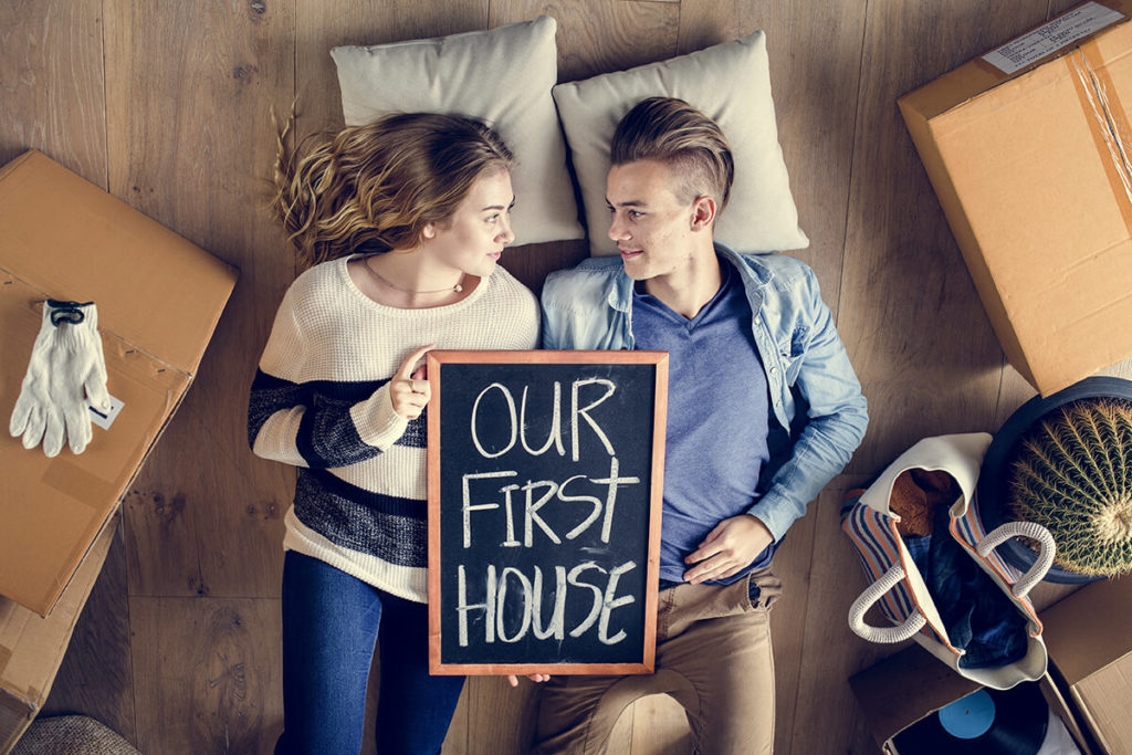 a couple holding a sign that says 'our first house' just after cross-country moving
